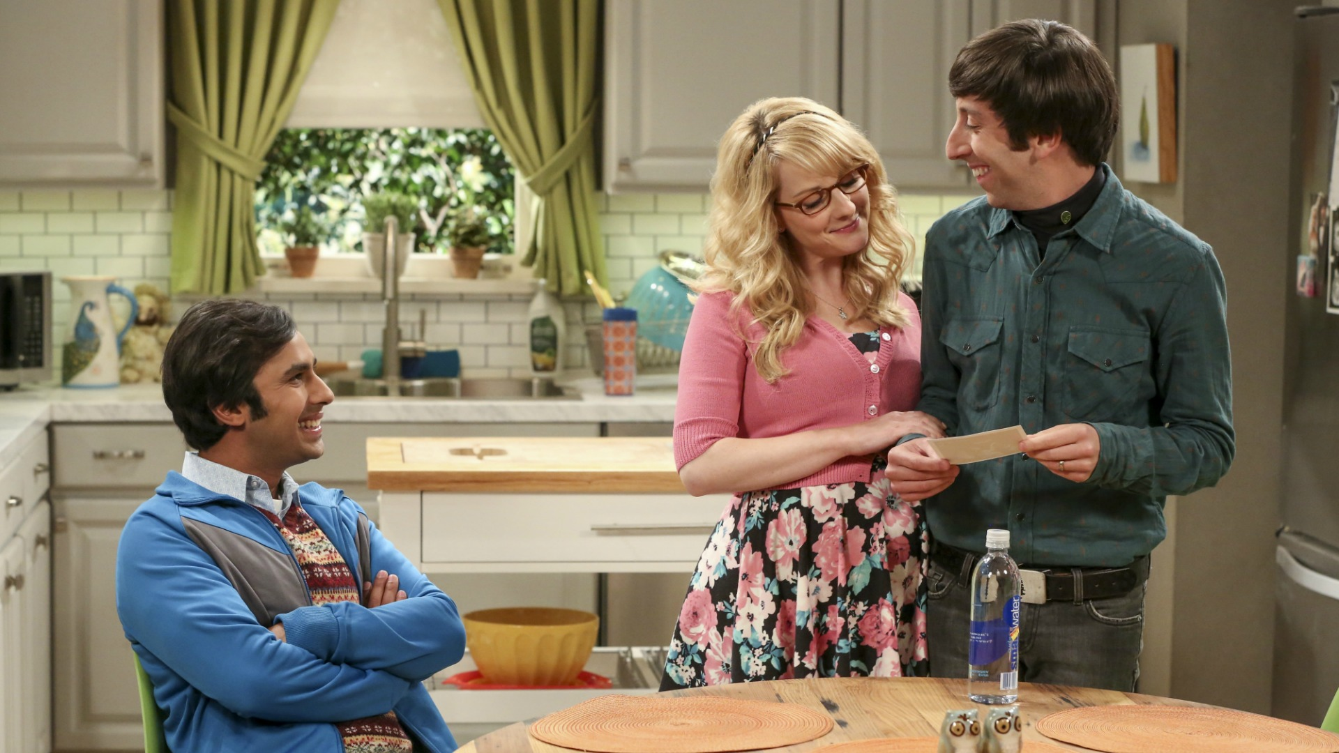 Howard and Bernadette share a sweet moment while Raj sits at the table.