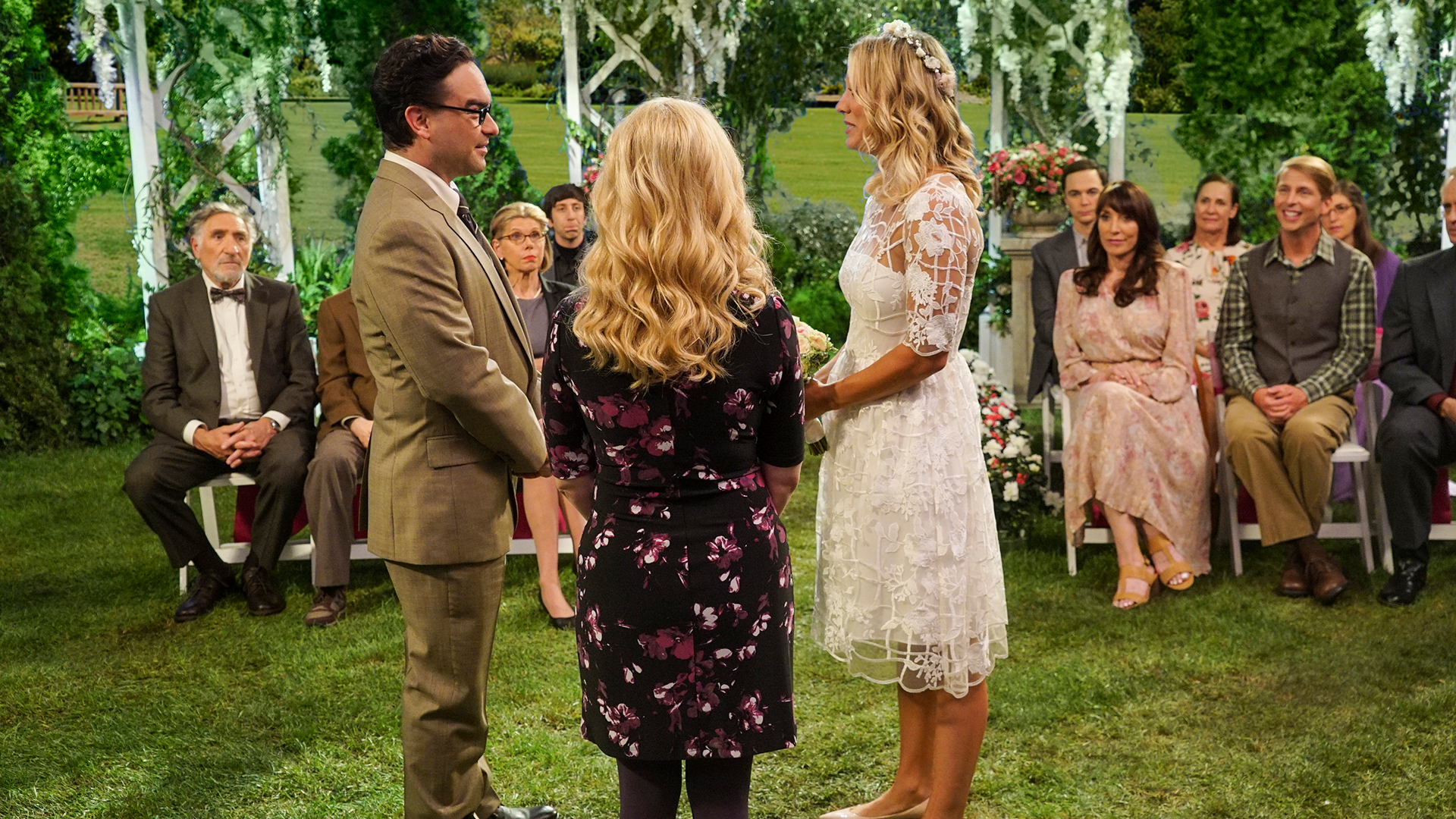 Leonard and Penny stand together in holy matrimony while Bernadette officiates.