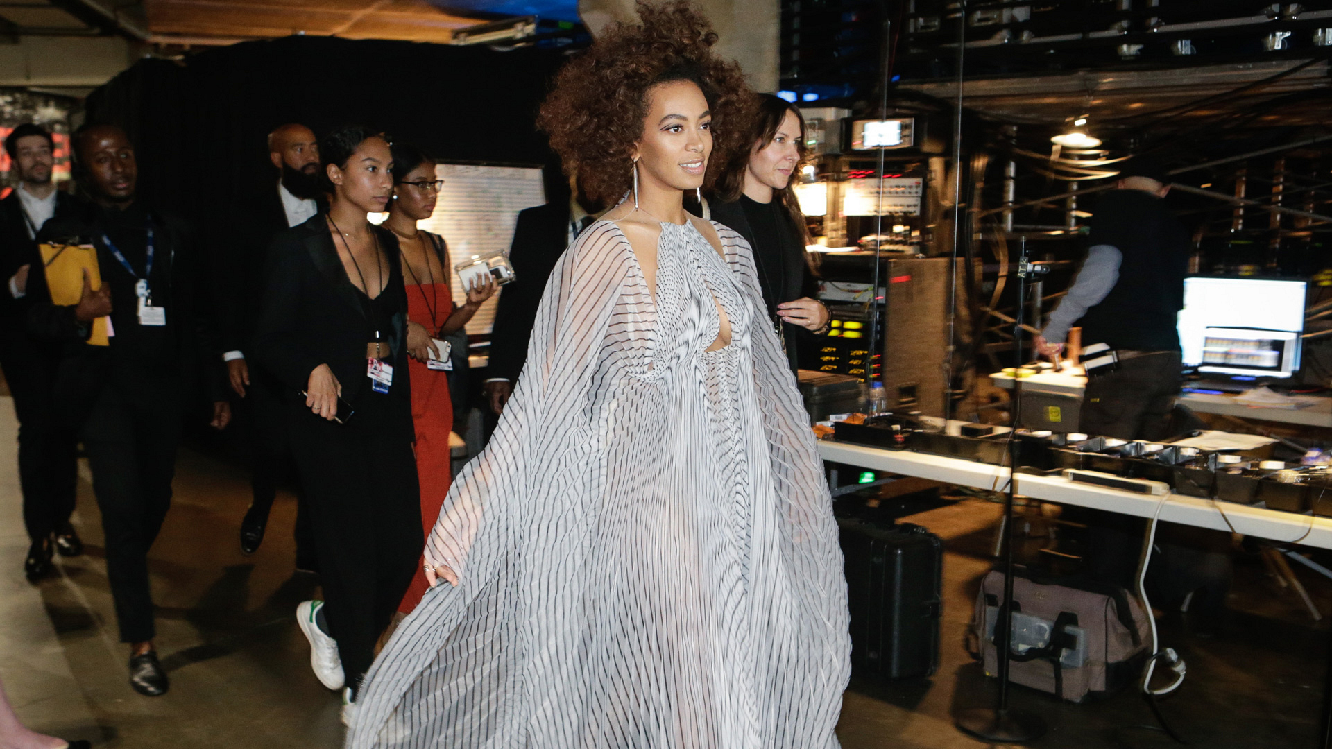 Solange appears to float through the GRAMMY backstage area in this striped statement dress.