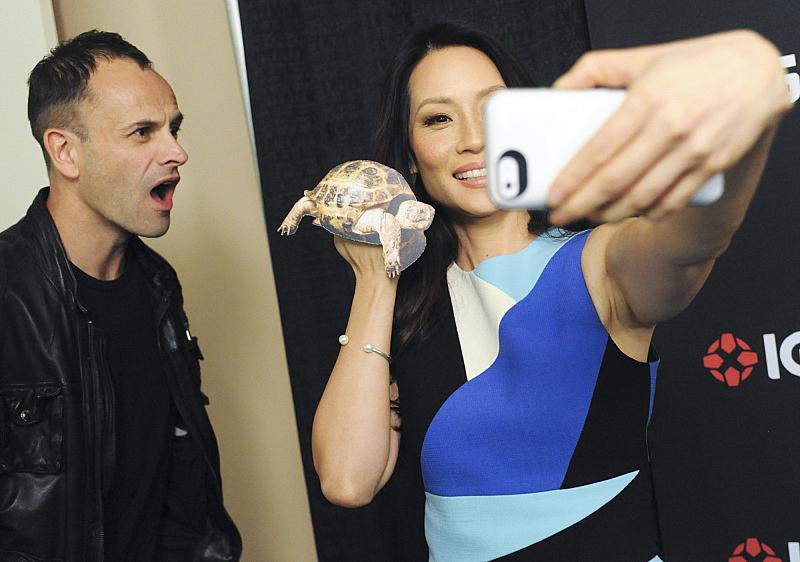 Jonny Lee Miller looks on as Lucy Liu snaps a selfie