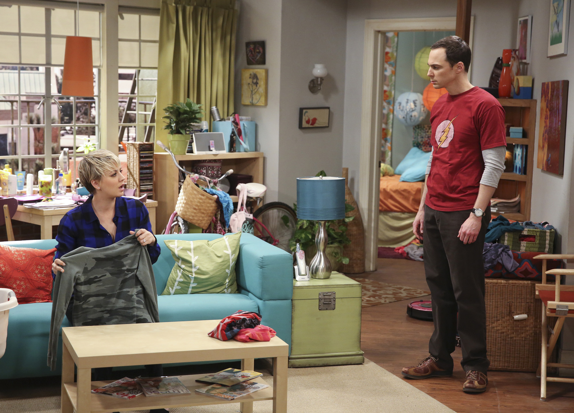 Penny folds laundry while talking to Sheldon