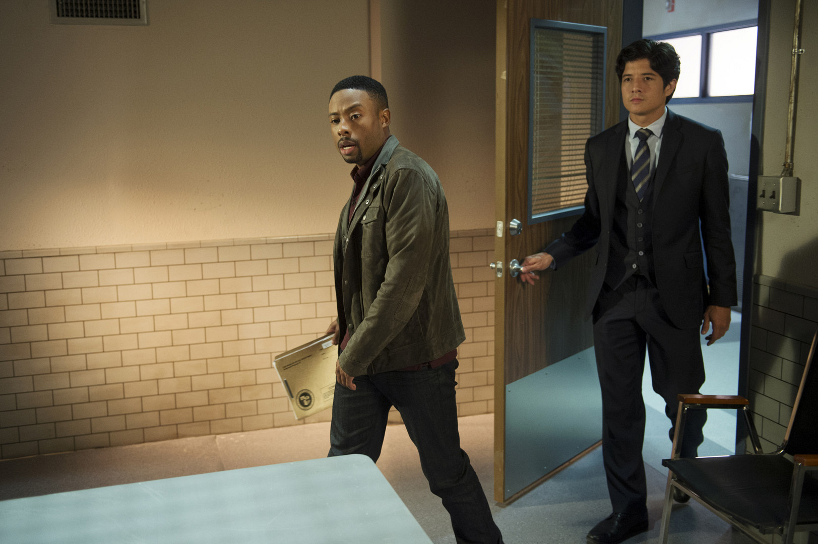 Carter leads the way into the interrogation room.