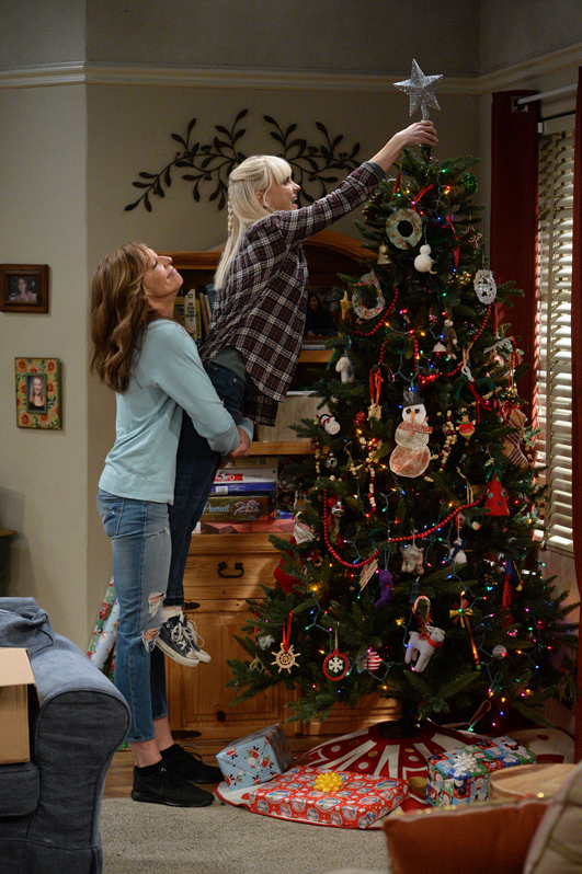 Bonnie helps Christy put the star on the tree.