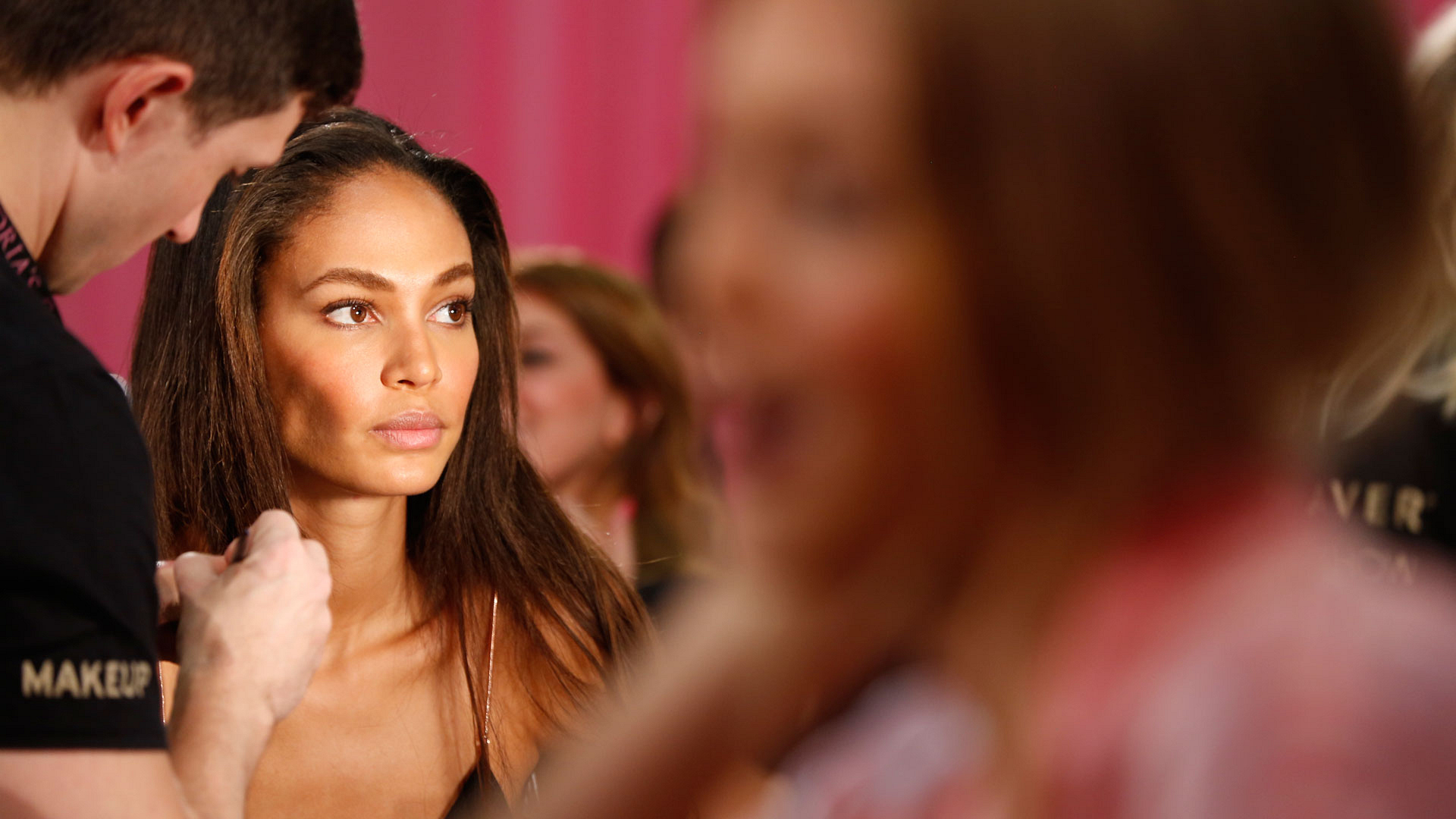 The makeup artists work away as Joan Smalls looks on