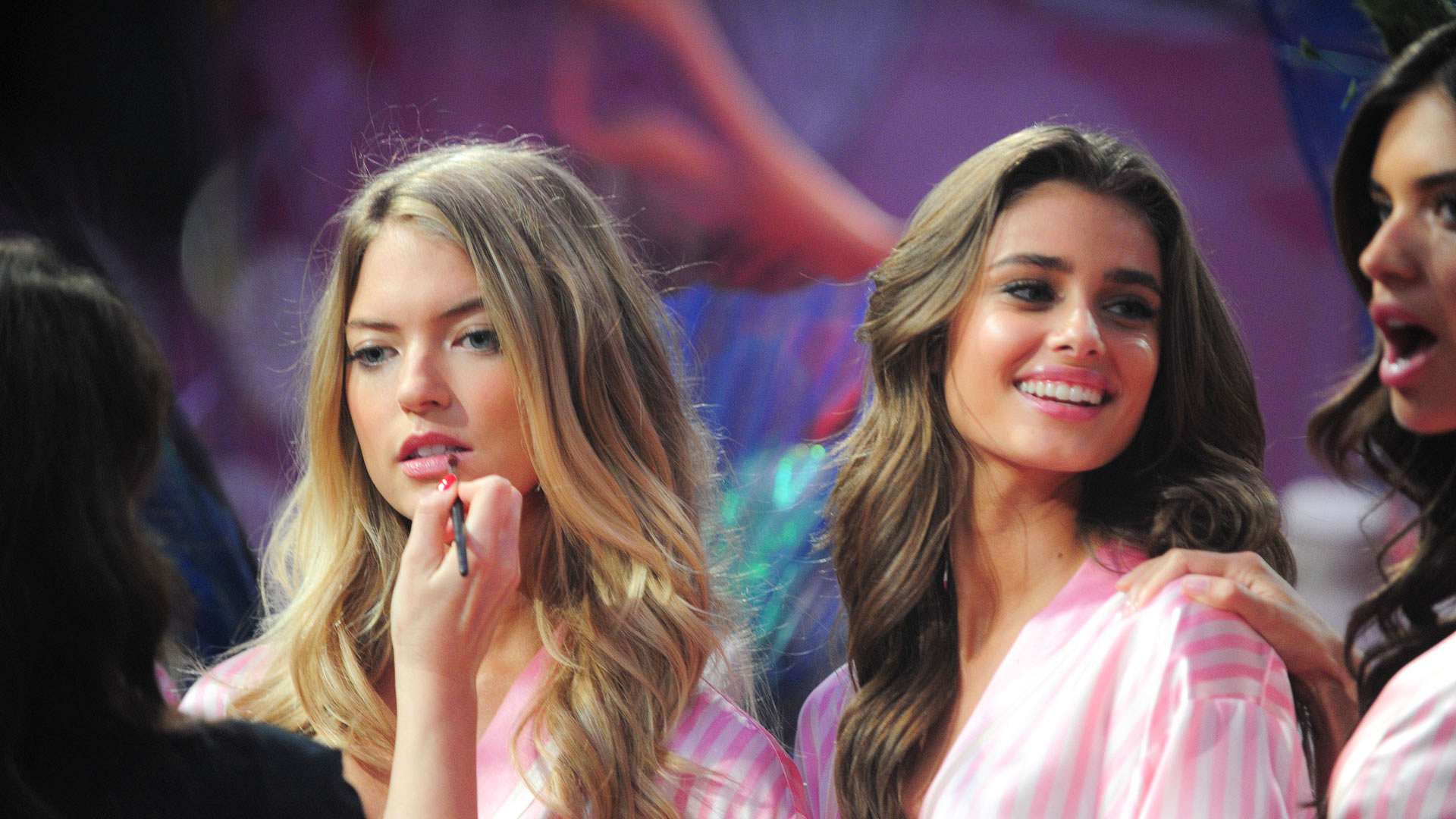 Martha Hunt gets a last-minute lip-gloss check while standing with Taylor Hill