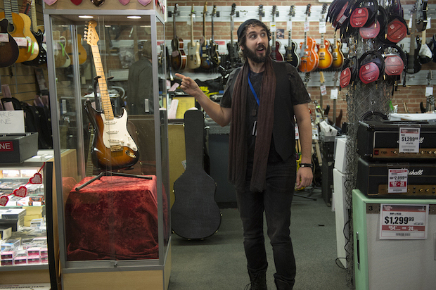 Ian, the overzealous guitar store salesman, shows off a special item.