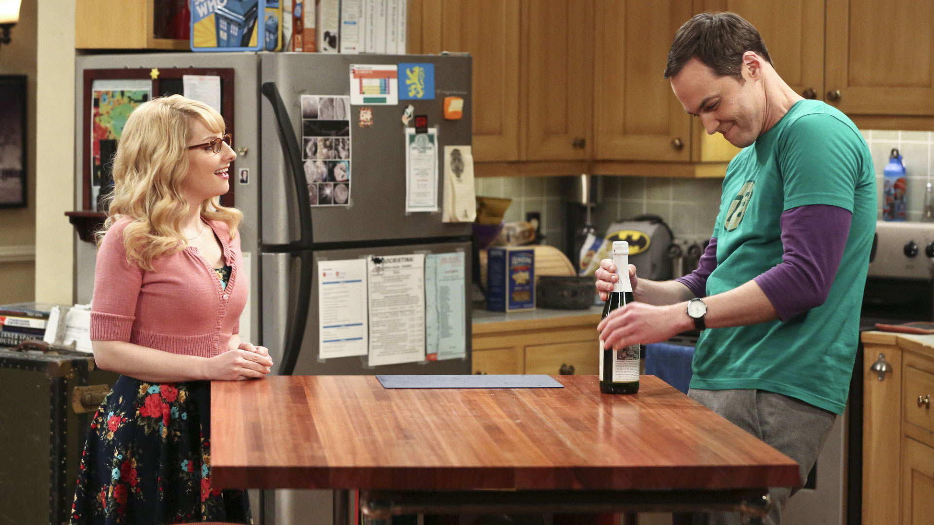 Sheldon opens a bottle of sparkling cider for Bernadette and himself.
