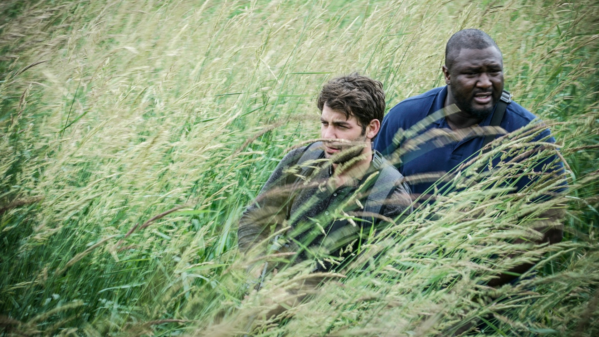 Jackson and Abraham move through high grass in their search.