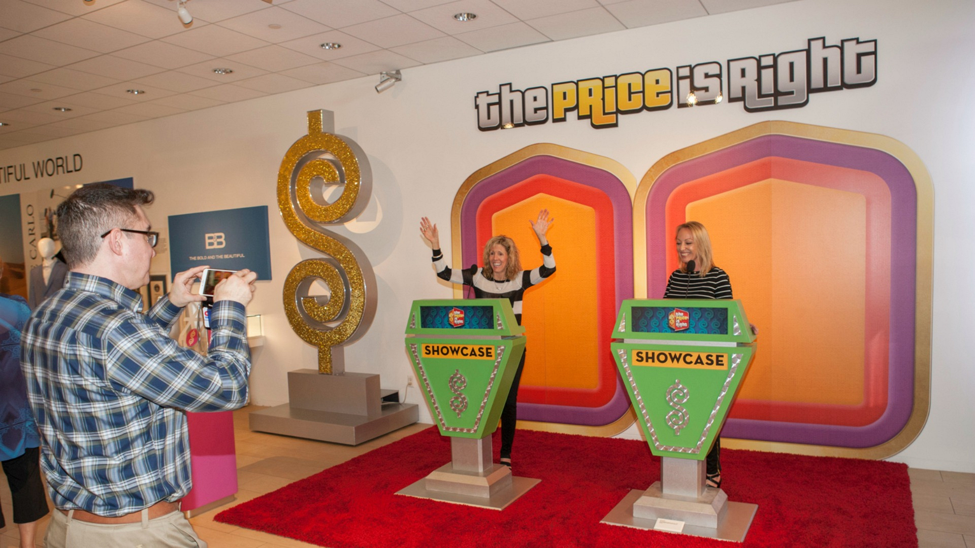 Two fans check out The Price Is Right Showcase podiums.