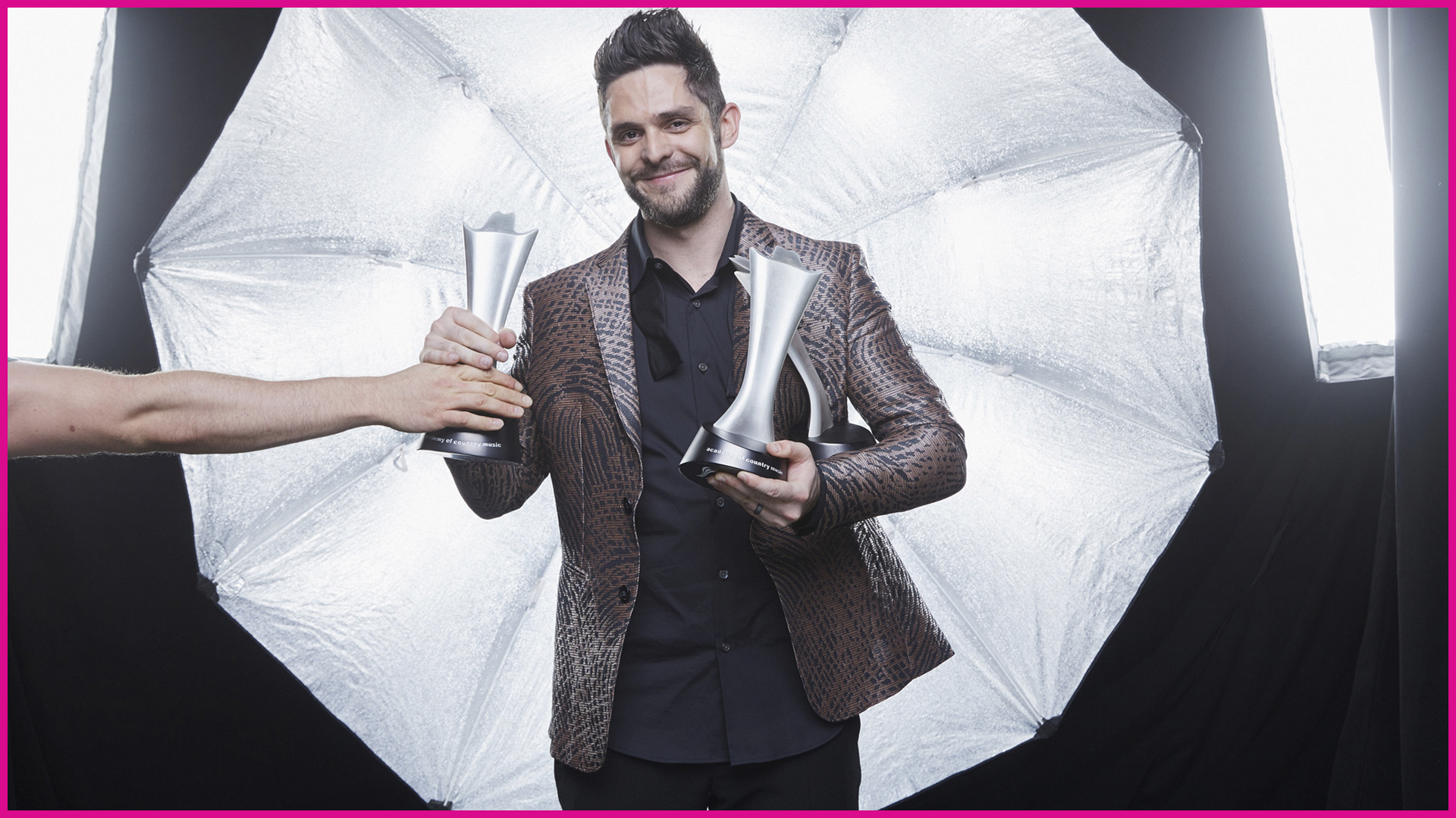 Thomas Rhett cradles two shiny ACM statues in his arms after a big night in Vegas!