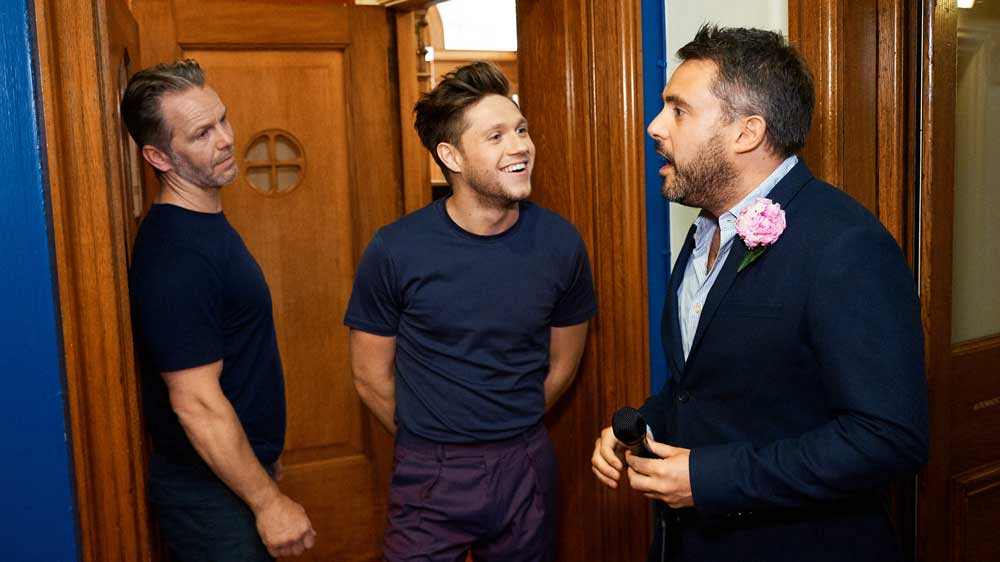 Niall Horan's bodyguard (left) is about to toss Louis Waymouth (right) outside.