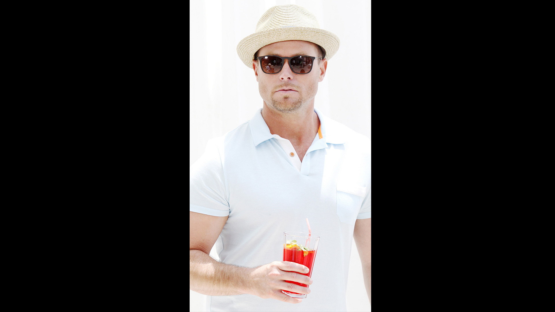 Jacob Young cools off with a fedora, shades, and delicious-looking beverage.
