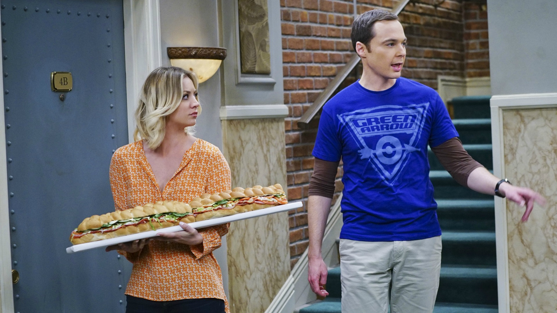 Sheldon and Penny take their large sandwich and storm across the hall.