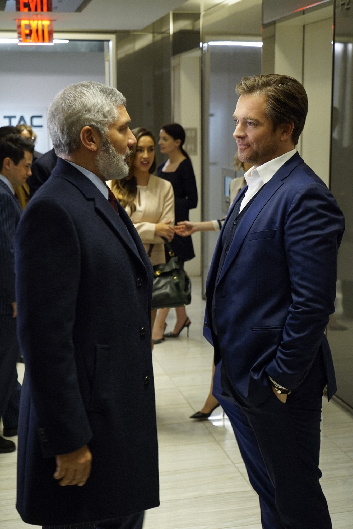 Dr. Bull meets with his client's lawyer in the hallway.