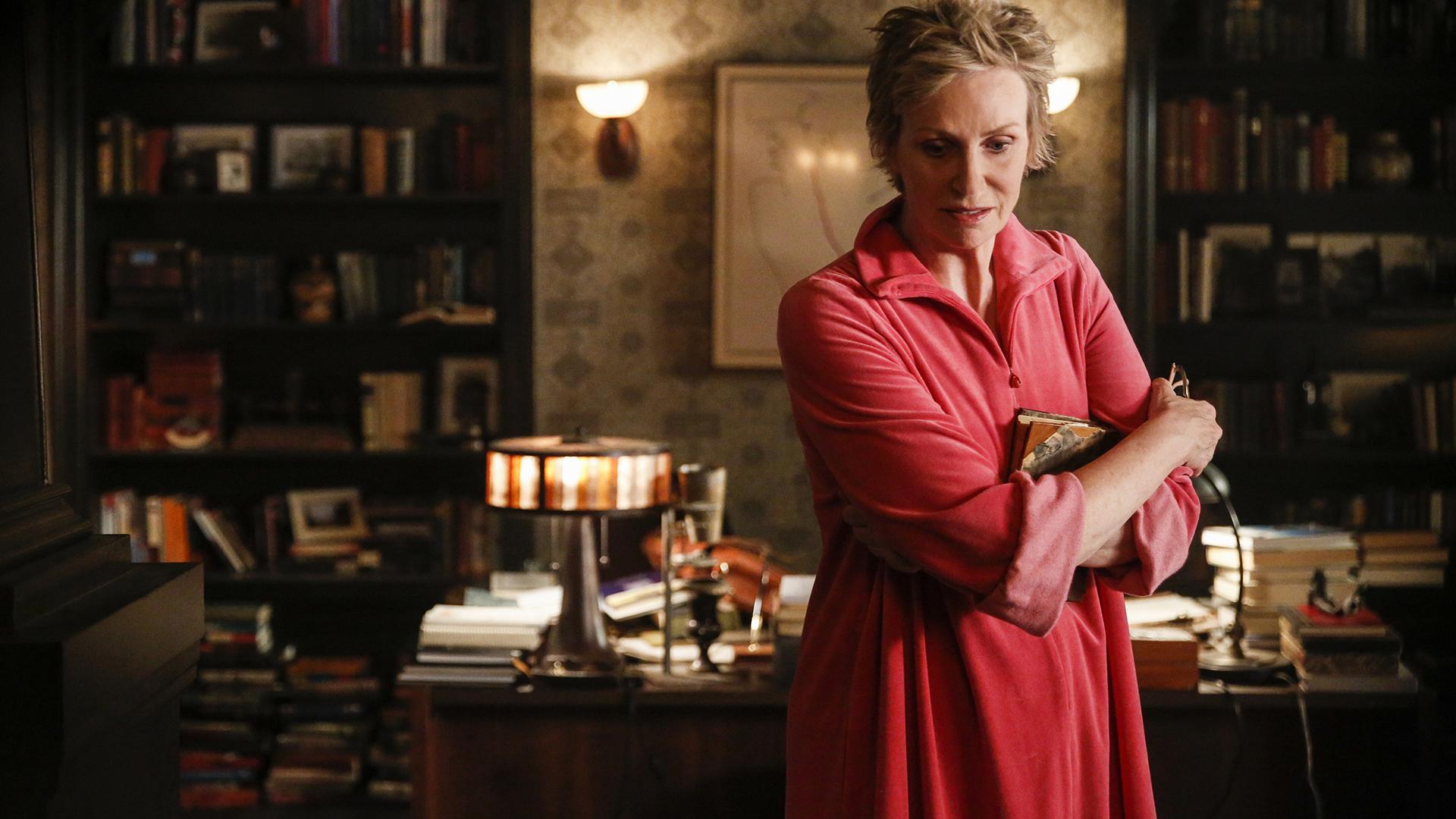 Diana clutches a scrapbook.