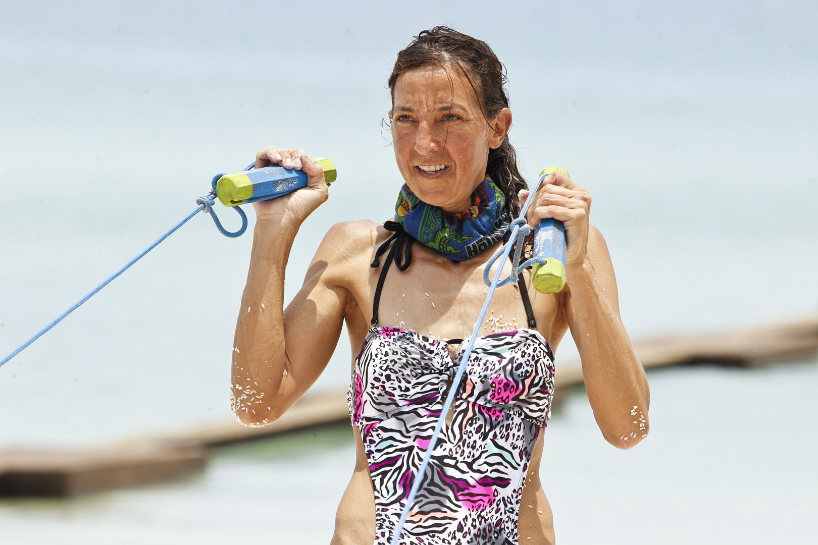 Debbie holds on tight while navigating through the challenge's final obstacle.