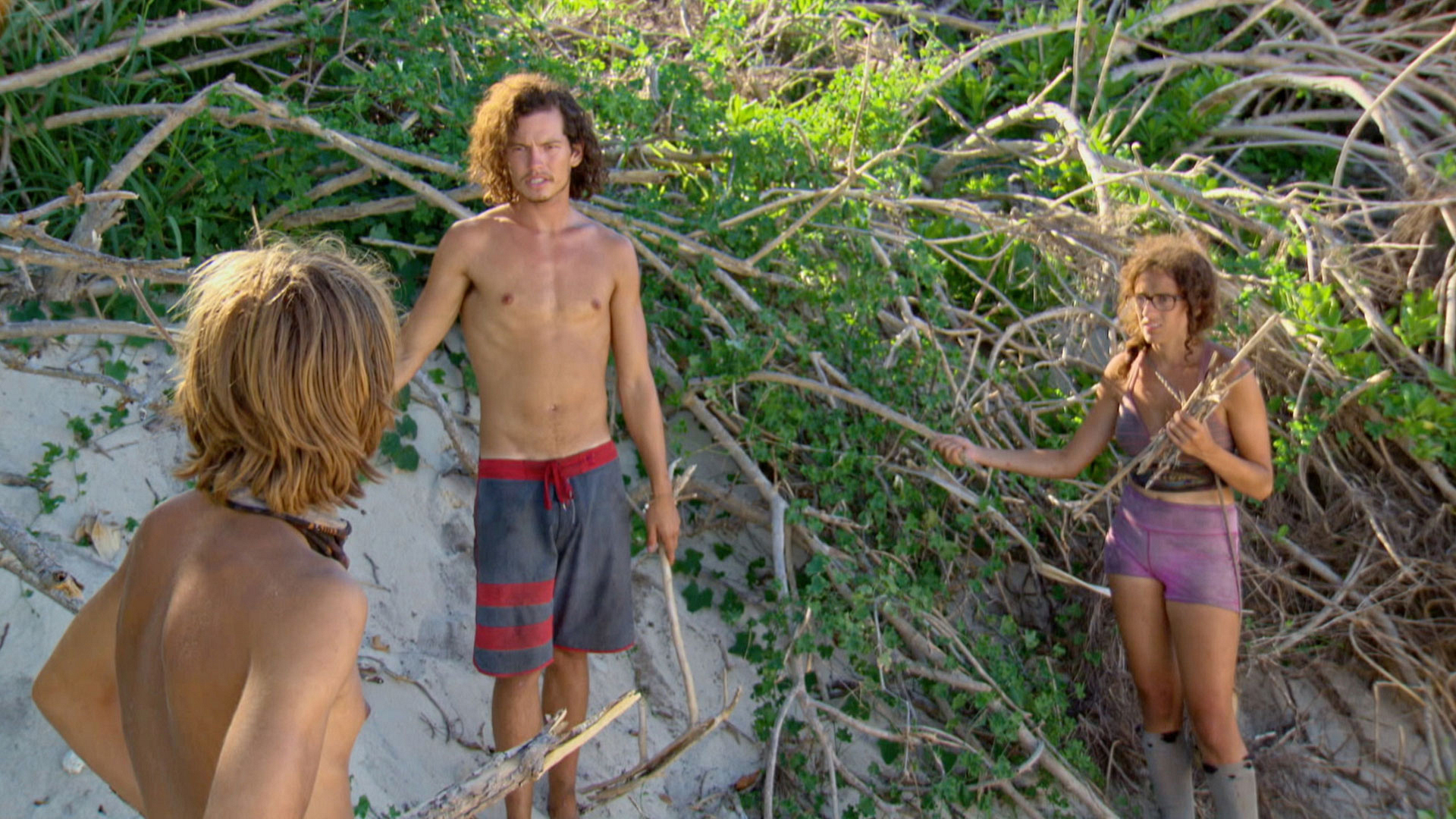 Will, Jay, and Hannah chat while they gather branches along the beach.
