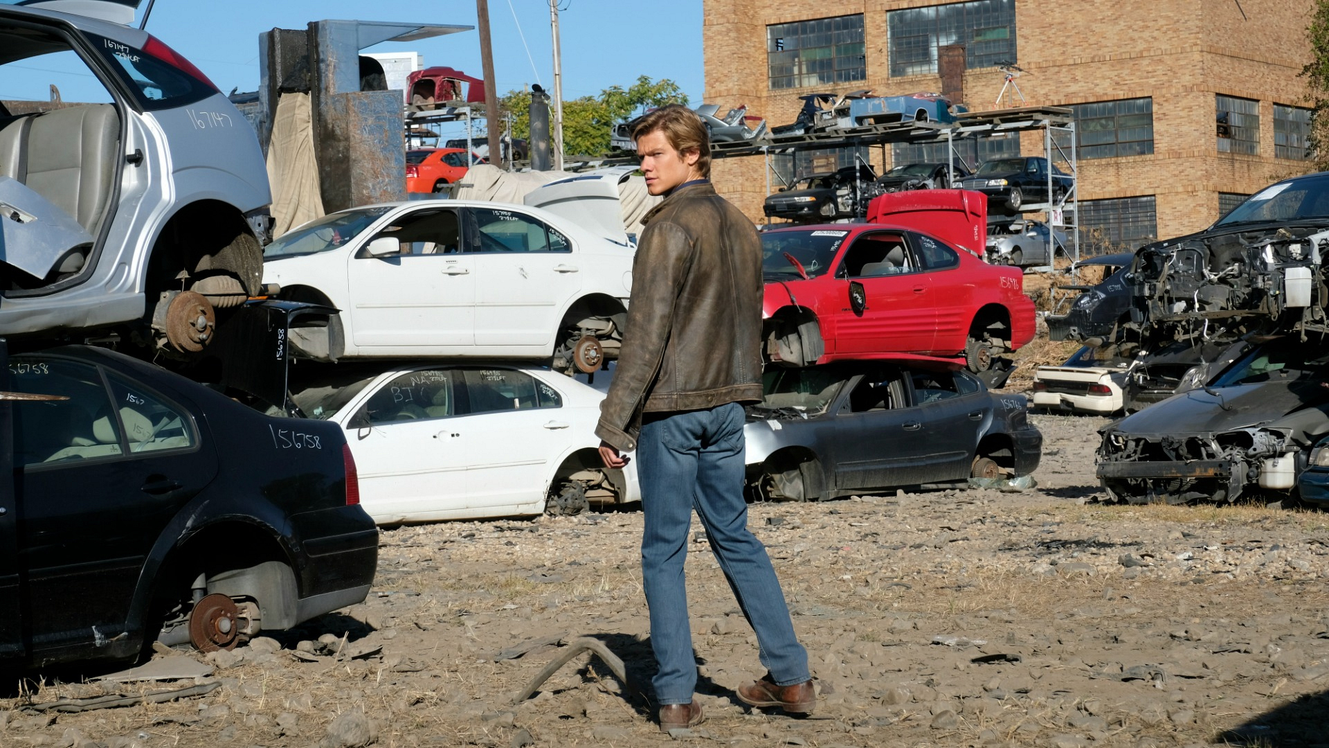 MacGyver surveys the junkyard.