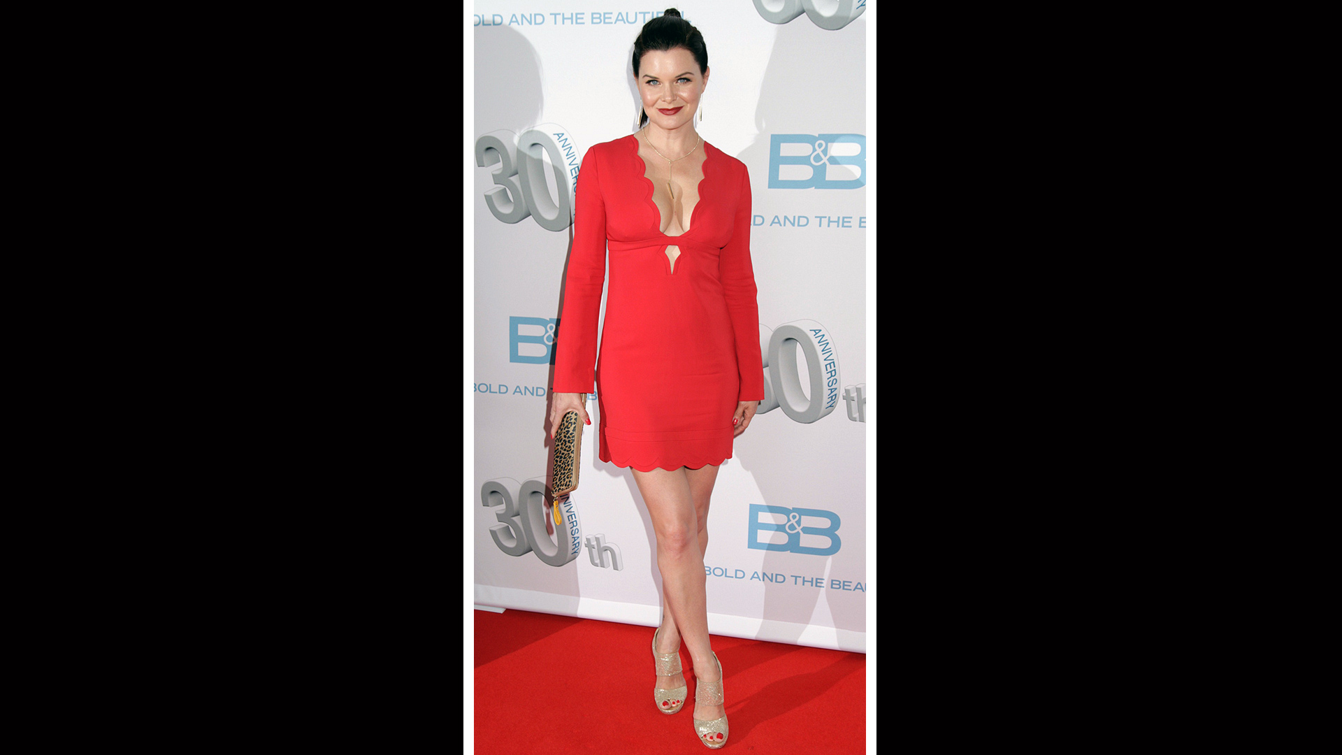 Heather Tom embraces spring in a bright red dress with a scalloped neckline.
