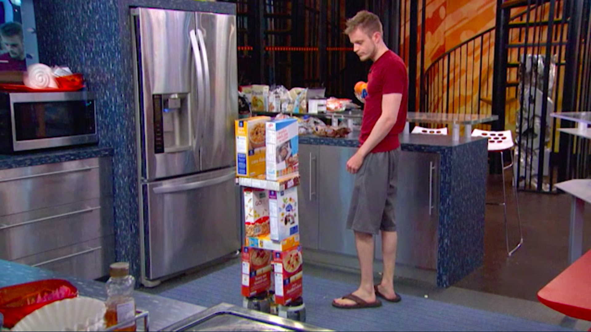 11. Johnny Mac stacks cereal boxes in the kitchen.