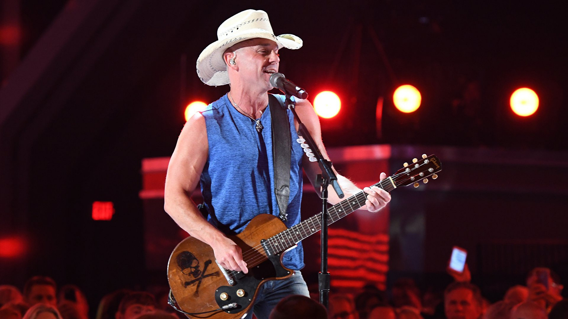 "A sleeveless Kenny Chesney hits the stage first and performs his latest single, ""Get Along."""