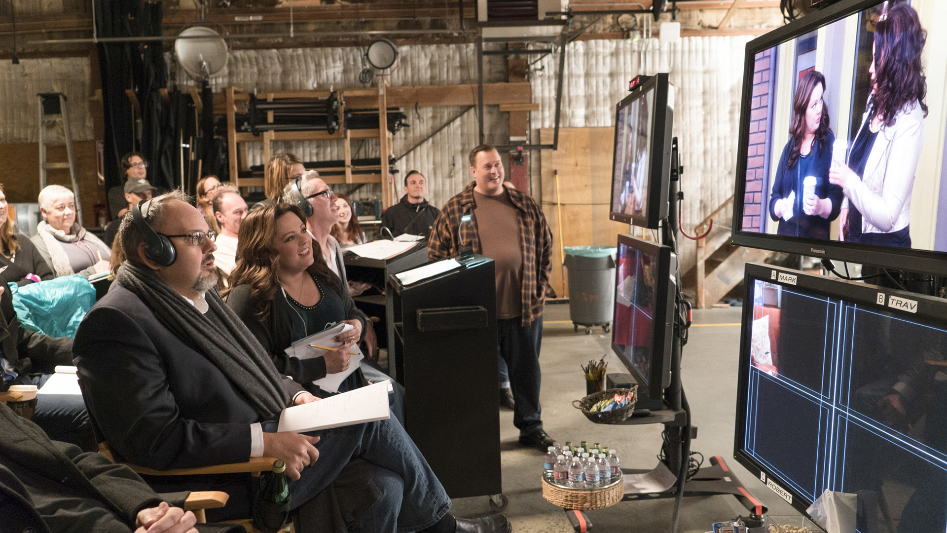 The cast and crew of Mike & Molly watch back a scene together on set.