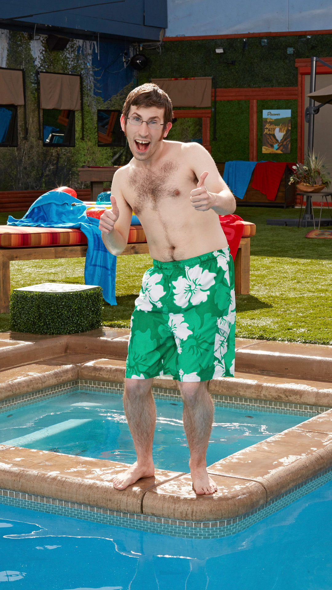 Scott parties poolside in green floral swim trunks complete with two big thumbs up.