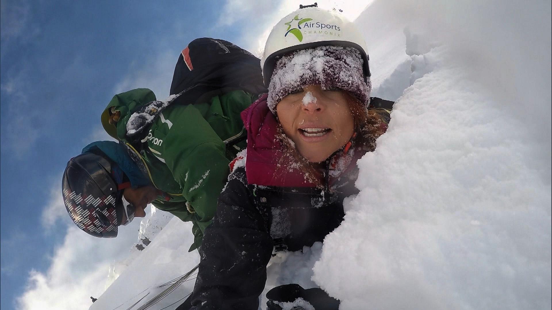 Erin must paraglide 7,000 feet over Chamonix in the Roadblock.
