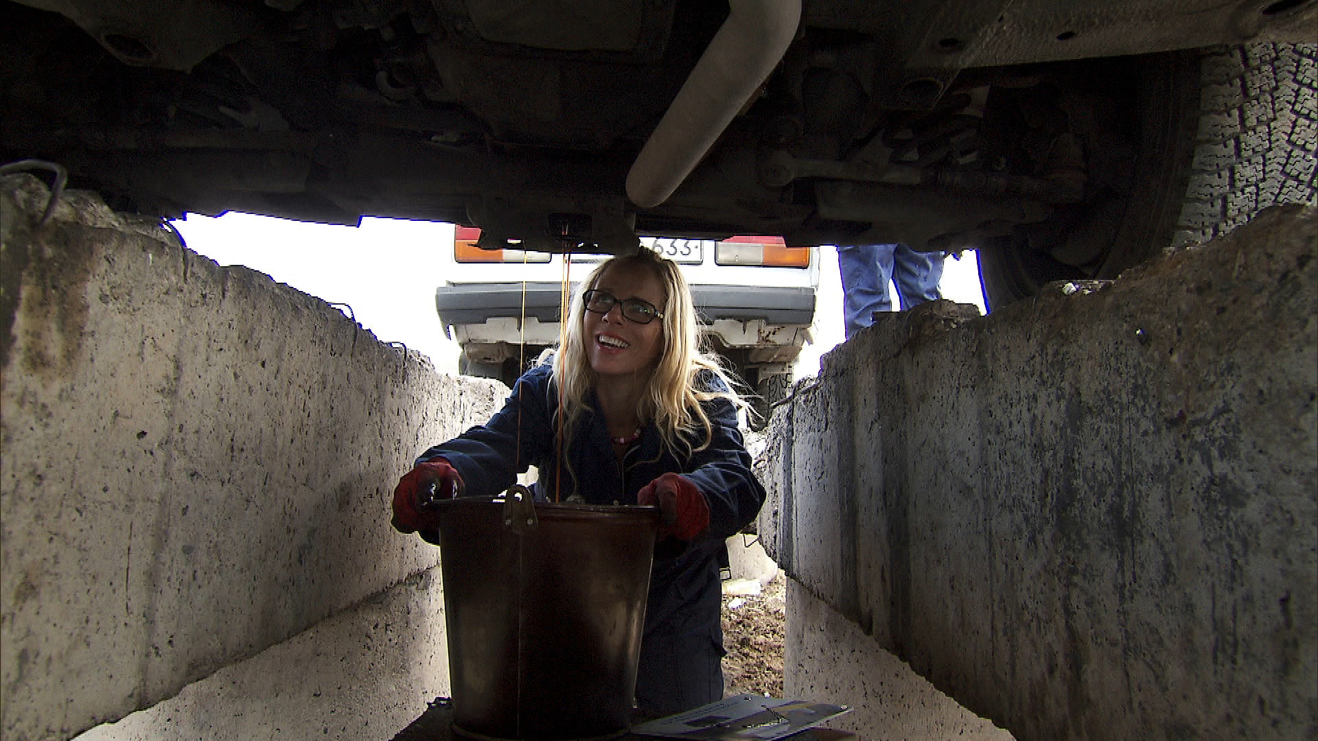 At the Roadblock, Sheri gets under the hood of a stopped taxi.