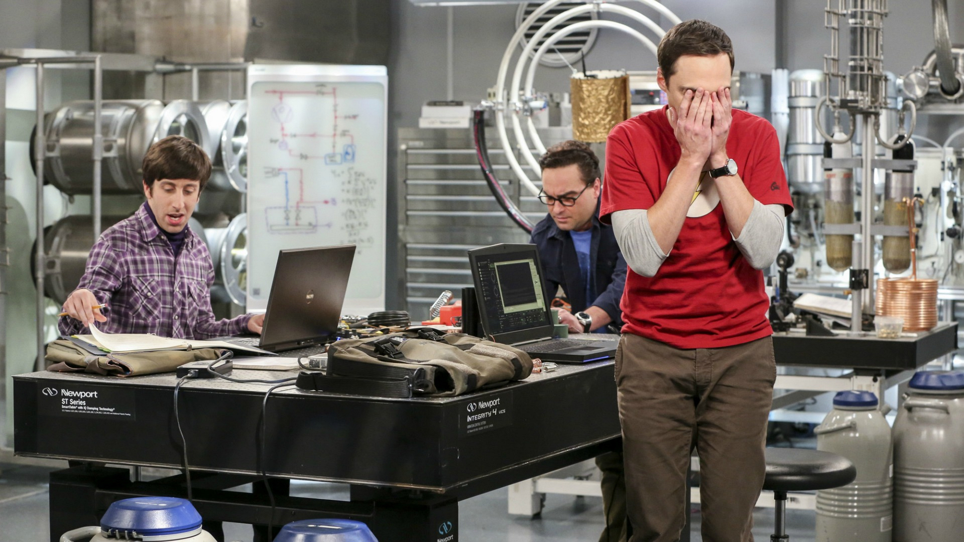 Sheldon covers his face while Howard and Leonard work.