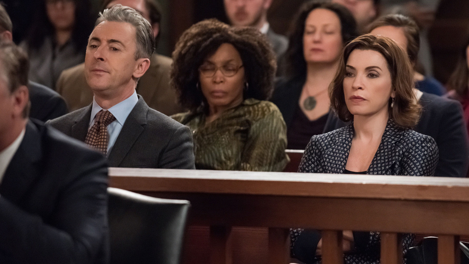 Eli Gold and Alicia Florrick look solemn in the courtroom gallery.