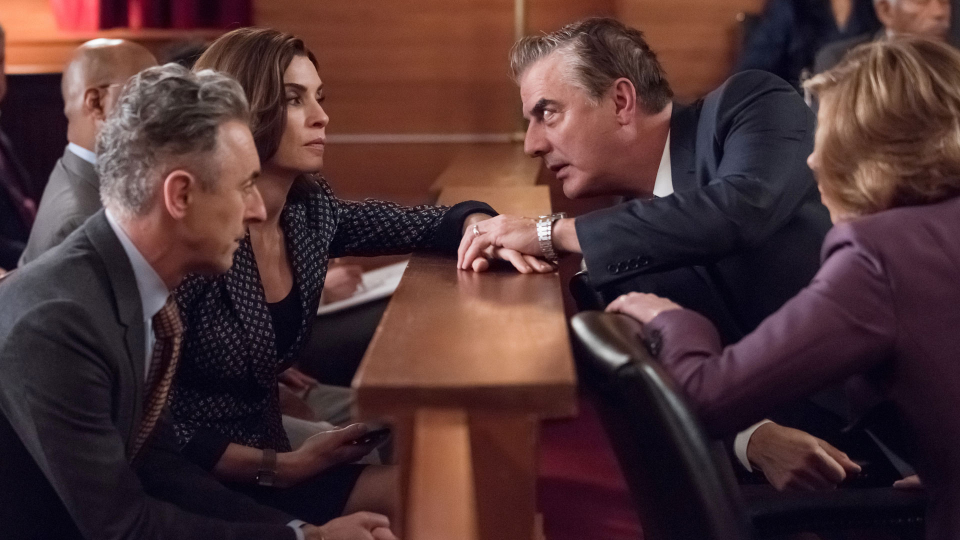 Peter grasps Alicia's hand in the courtroom.